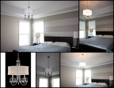 The master bedroom with a chandelier light with a shade.