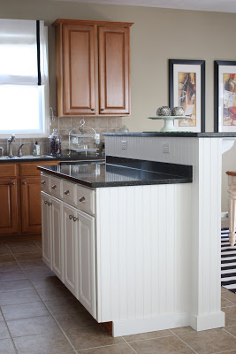 Brown kitchen cabinets and a white modified island.