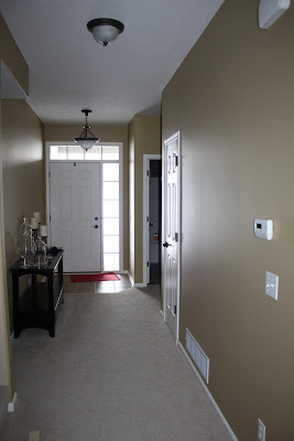 Long hallway painted off white with a white door at the end.