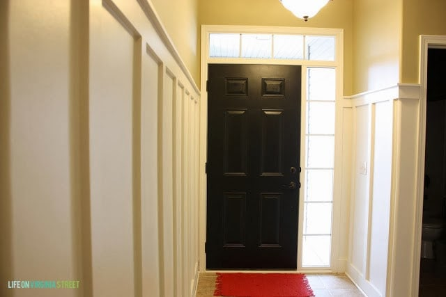 The door painted black with the light on in front of it.