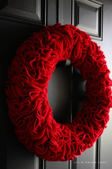 A gorgeous red ruffle wreath made with felt! Get the full tutorial on how to make this darling decor piece!