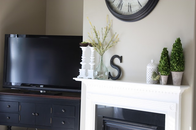 A spring mantle with topiaries, glass vase, and a clock above the fireplace.