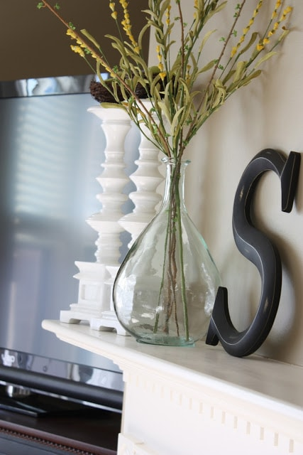 Glass bottles with sprigs of yellow flowers beside an S on the fireplace mantel.