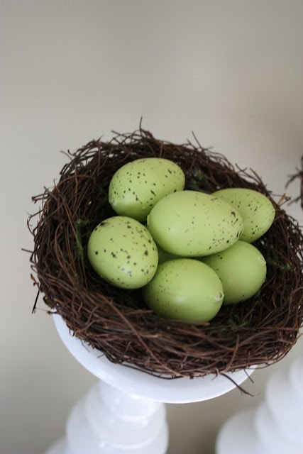 A twig bird nest with faux green bird eggs in it.