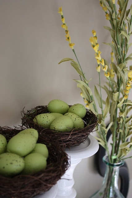 Spring mantle details with birds nests and yellow flowers in a glass vase.