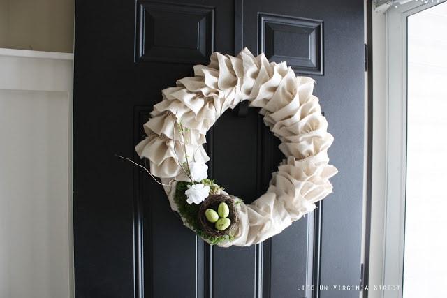 A white wreath hanging on a black door and the door is open.