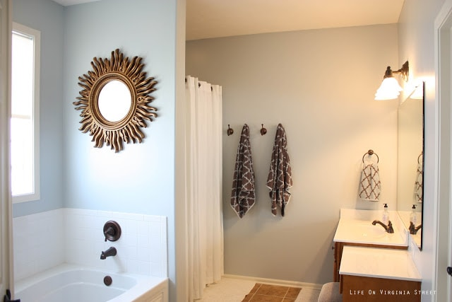 Master Bathroom painted Light French Gray by Behr and towel hooks with brown and white towels on them.