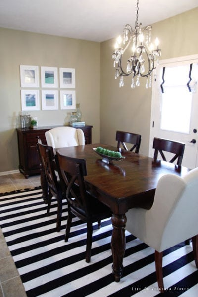 Dining Room with black and white striped rug, wood table, linen chairs, iron and crystal chandelier and beach photograph art.