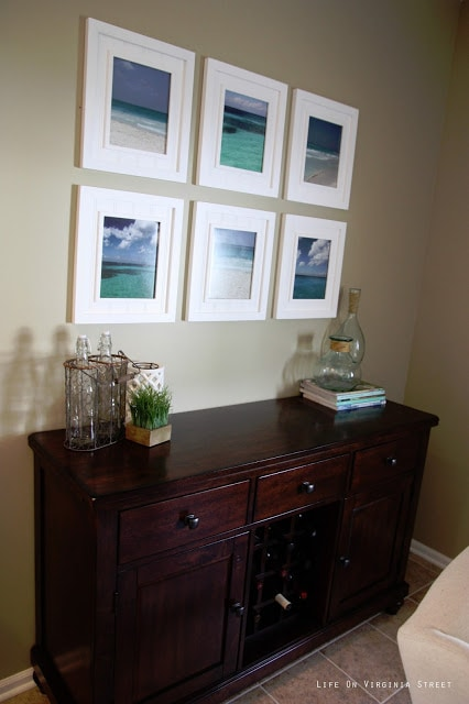 Dining room buffet table with beach art gallery wall.