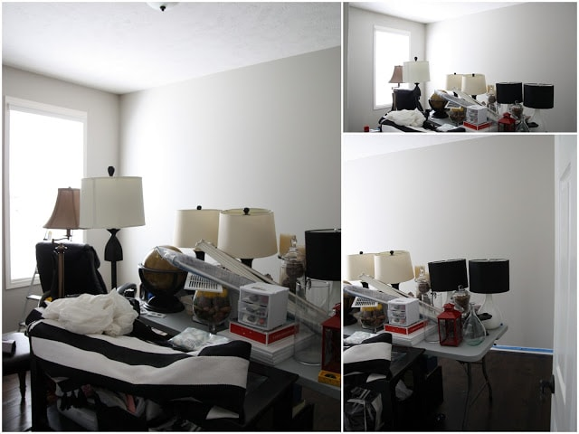 The room painted white with all the stuff in the middle of the room piled up.