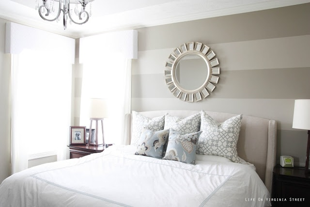 Bedroom with striped walls, white bedding, blue and gray pillows and chandelier.