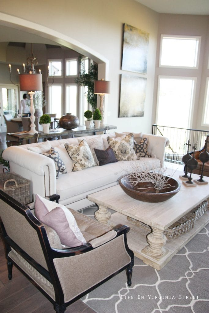 Gorgeous French-style living room with driftwood pillar coffee table, linen chesterfield sofa, gray and tan accents.