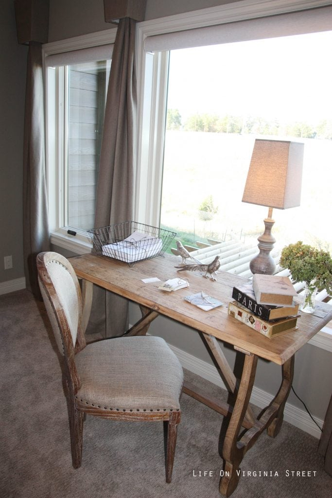 Writing nook in master bedroom with French-style desk and linen chair.