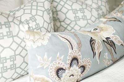 Soft blue and white floral pillows on the bed.