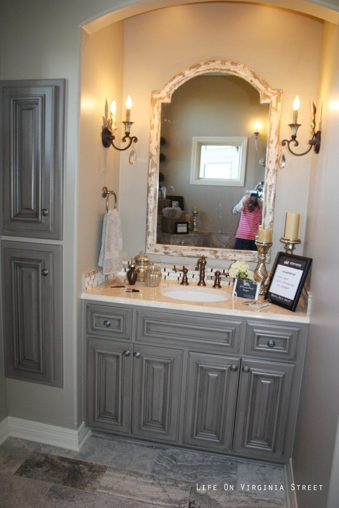 French-style master bathroom with gray painted vanity and candle sconces.