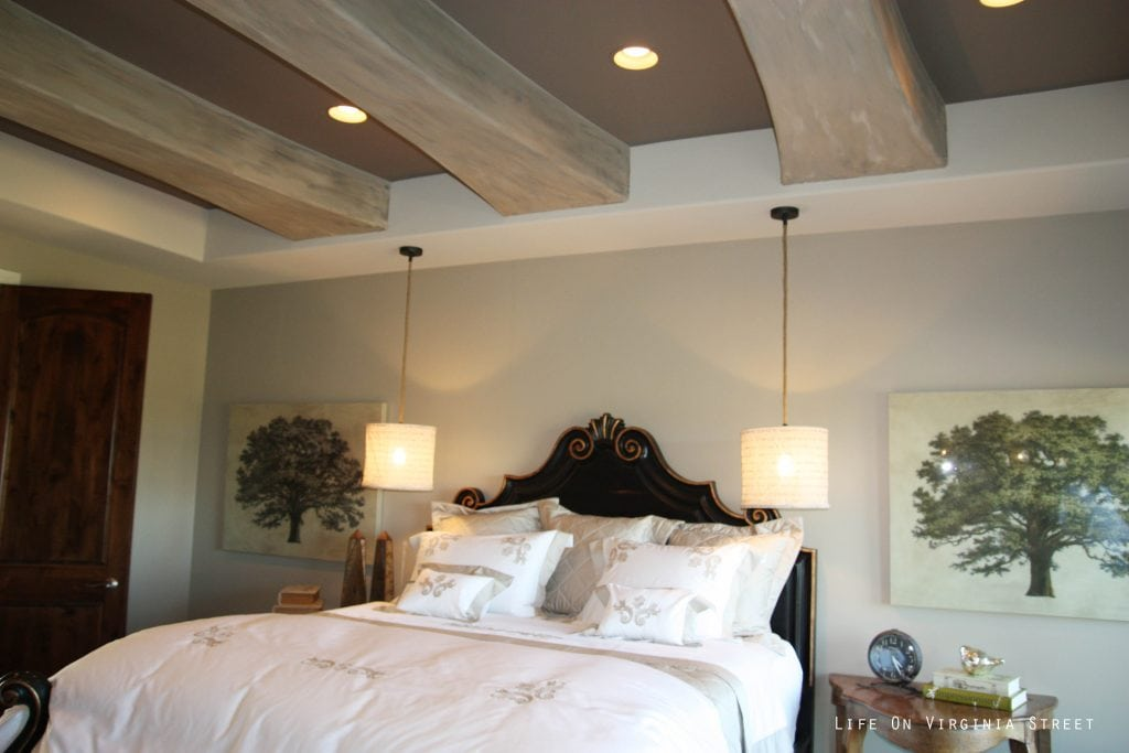 Master bedroom with faux wood beams on ceiling and hanging pendant lights over nightstand.