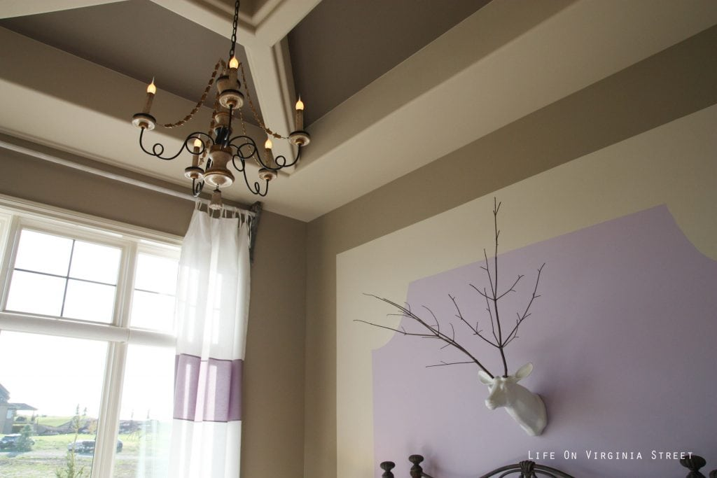 Girls bedroom with tan walls and lavender accents. Faux deer head with stick antlers and French chandelier.