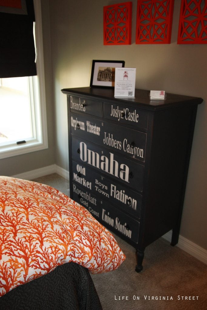 Black and white dresser with Omaha landmarks in a orange coral and navy blue bedroom.