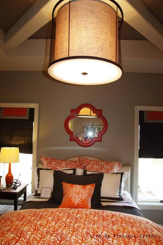 Orange coral and navy blue bedroom with linen caged chandelier.