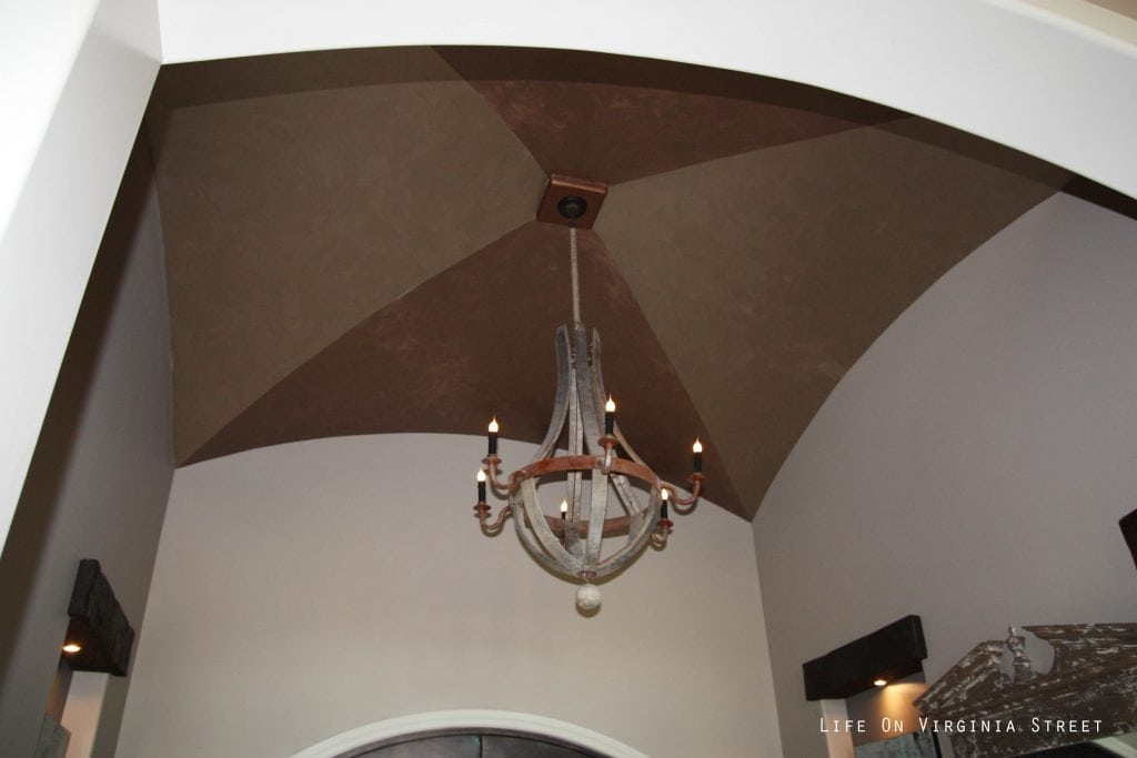 Wine barrel chandelier in a vaulted entryway.
