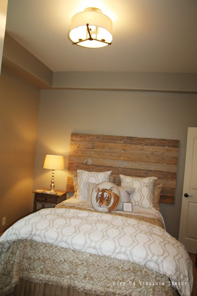 Neutral bedroom with wood pallet headboard, white trellis bedding and tiger throw pillow.