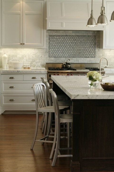 Kitchen island with a marble top and pendant lights over top of it.