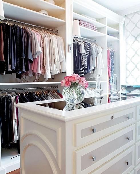 A white closet with a white closet island and pink flowers in a clear vase on it.