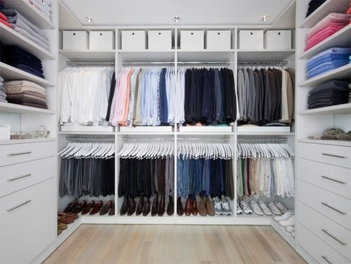 Large closet with organized mens clothes and shoes.