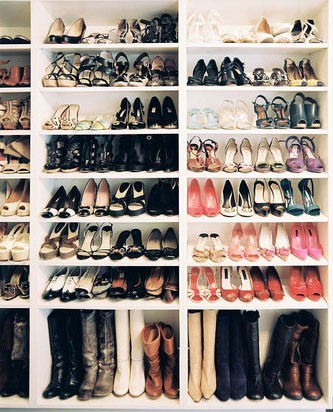 Shoe closet with built in shelves and shoes and boots on the shelves.