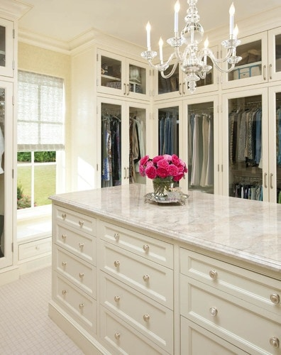 Closet with marble island and chandelier.