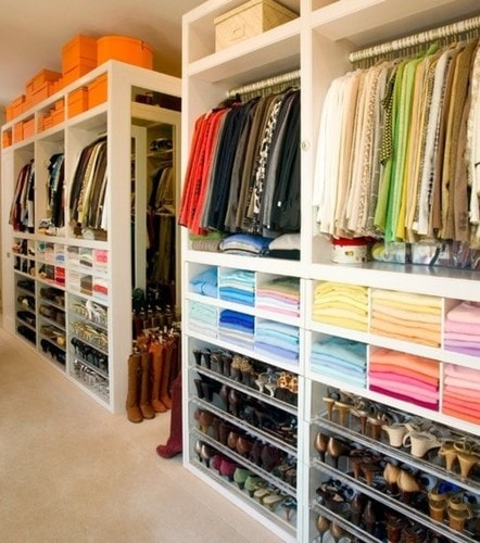 A walk in closet with multiple shelves, and shoes and boxes.