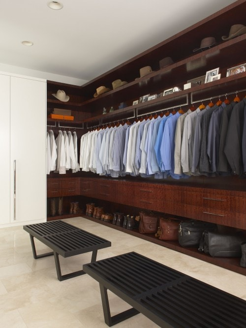 A dark wood closet with mens clothes.