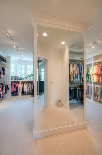 Walk-in closet with windows and full-length mirror.
