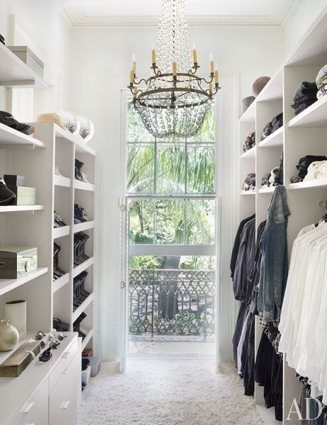 White closet with chandelier and windows.