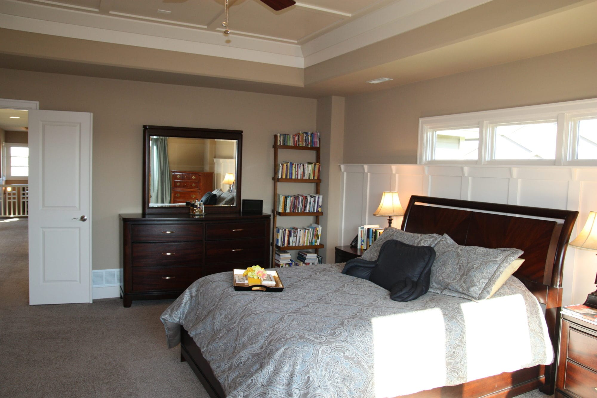 A large bedroom with a dark wood bed, dresser and door opened to the hallway.