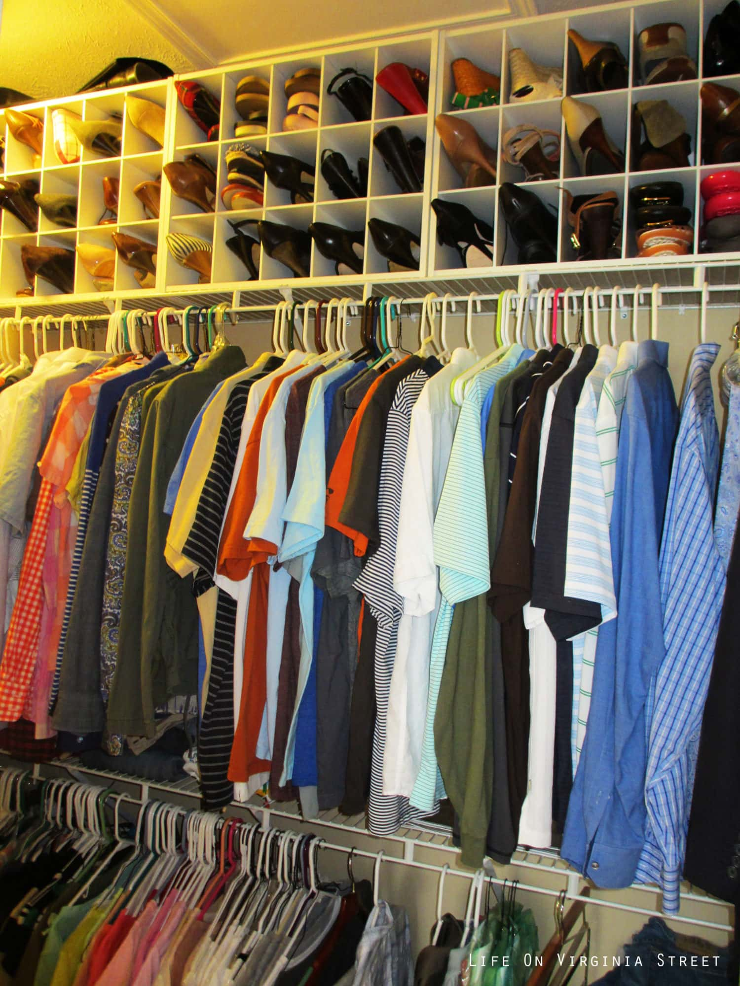 A close up picture of the shirts and shoes in the closet.