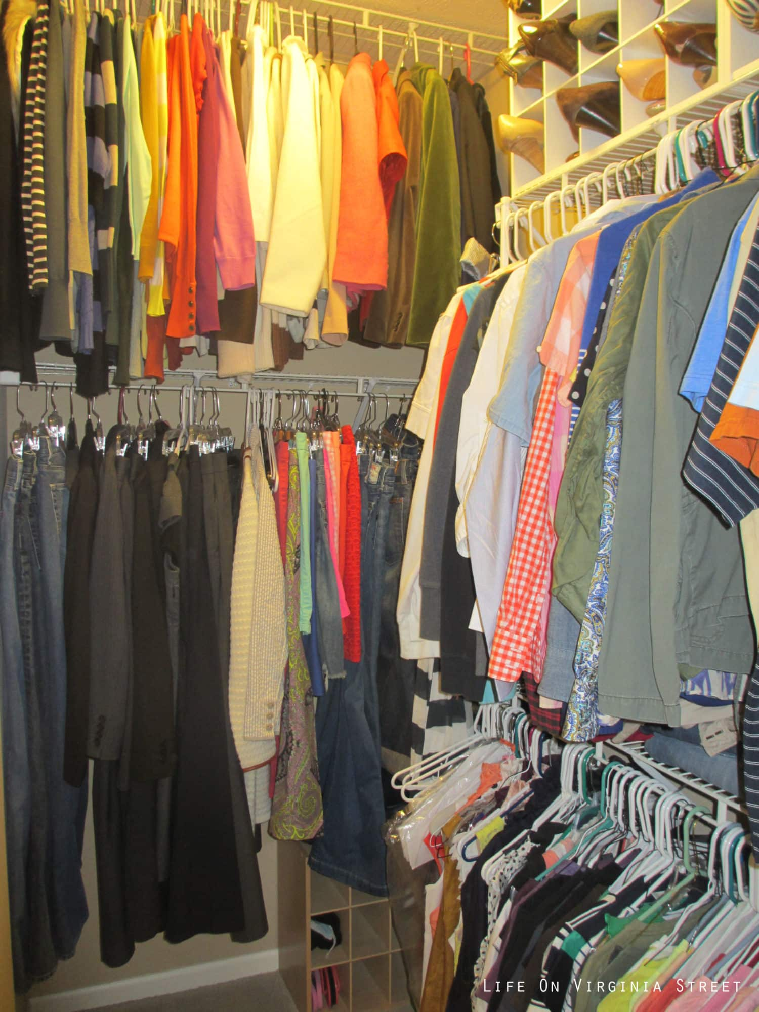 A crumpled closet with clothes hanging up and shoes above the clothes.