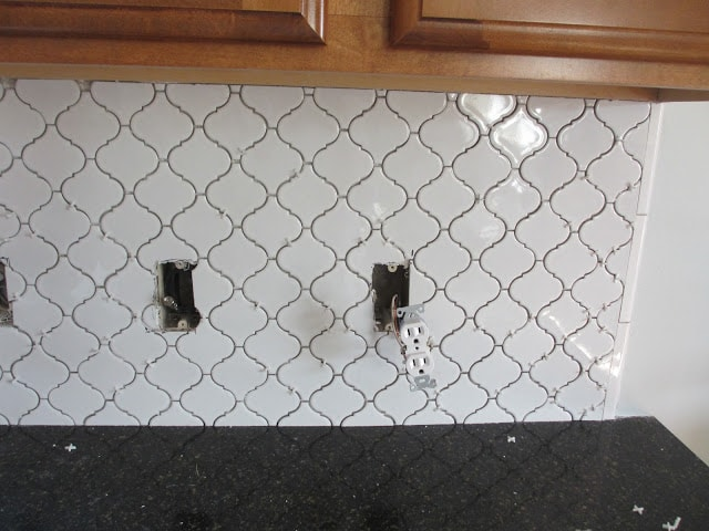 White Moroccan Tile backsplash ungrouted on the wall with electrical sockets hanging out.