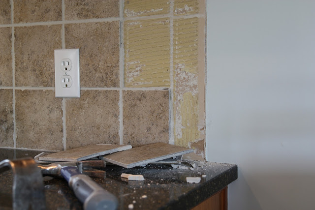 Removing ceramic tile backsplash with a hammer on the counter.