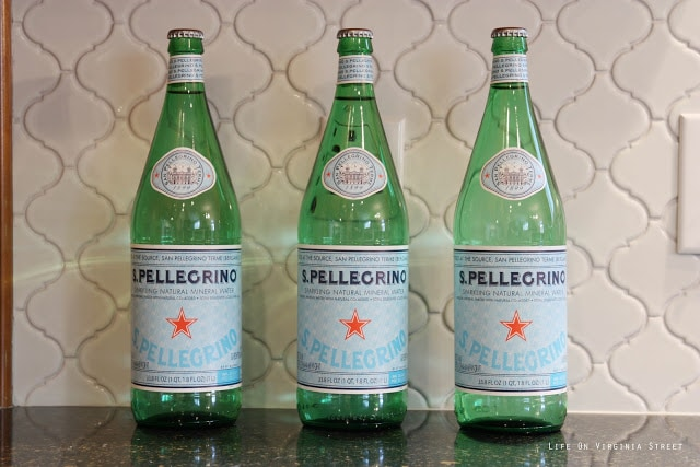 White Moroccan Tile backsplash in kitchen with Pellegrino bottles in front of it on the counter.