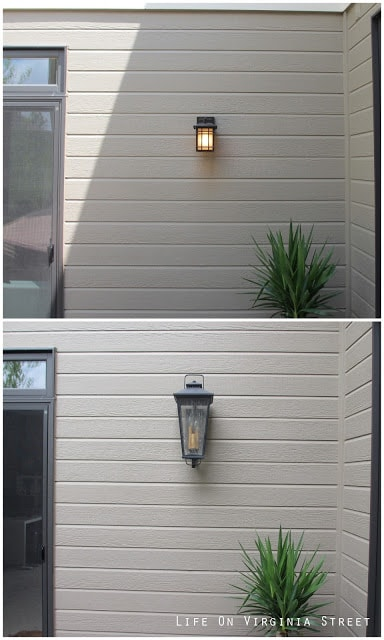 A small square light and a larger lantern light on the side of the house.