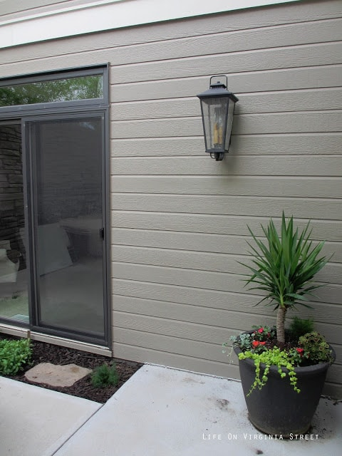 A light fixture and a planter on the side of the house.