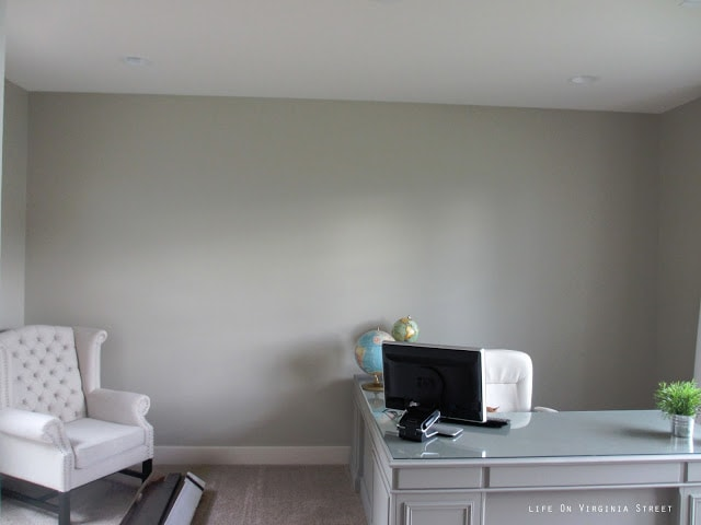 An empty room with a blank wall and a white chair in the corner of the room.