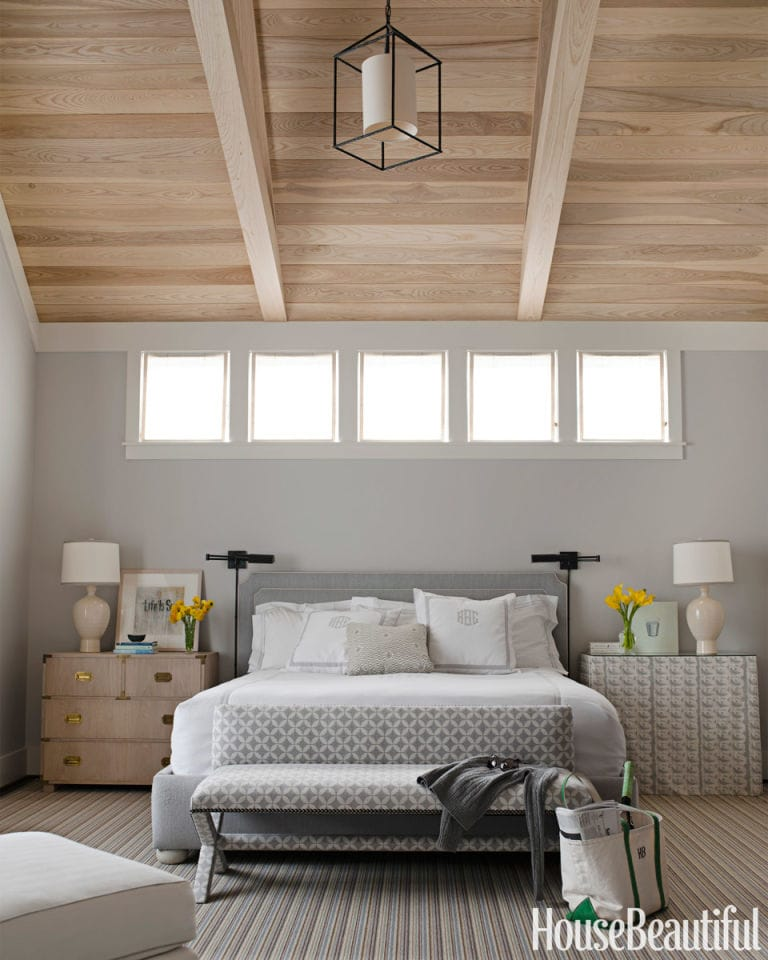 Wood beams on the ceiling, gray bed, gray walls, and side table with lamps on them.