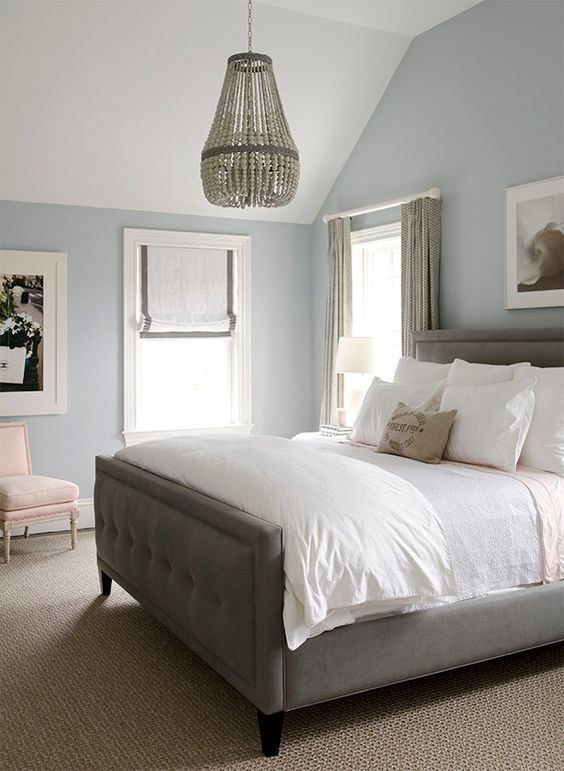 Gray blue walls, gray bed with white bedding and a wooden chandelier above bed.