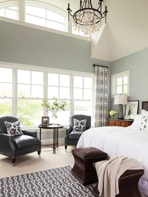 Large, full-wall windows, rustic black chandelier above bed, gray and green on walls.