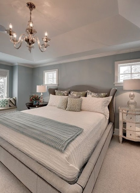 Blue gray bedroom walll color with white trip and chandelier above bed.