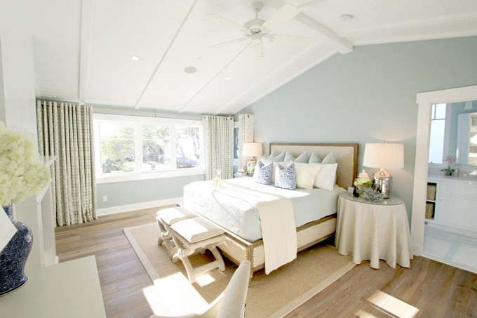 Turquoise green room, light beige bed, side table with beige tablecloth, and footstools at the head of the bed.