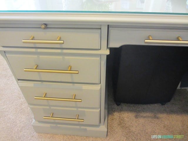 A five drawer desk with the new gold handles on.
