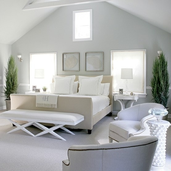 Light blue walls and neutral bedding in an A shaped master bedroom.